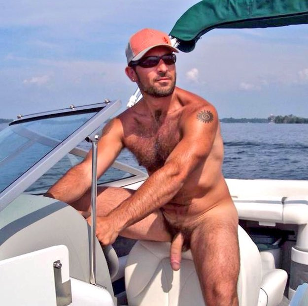 Nude guy driving boat